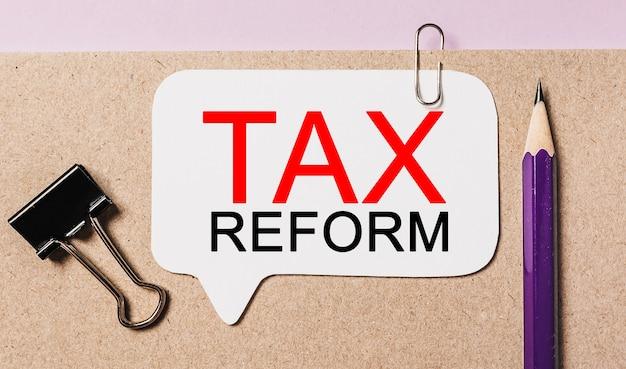 Texte de la réforme fiscale sur un autocollant blanc avec espace de papeterie de bureau