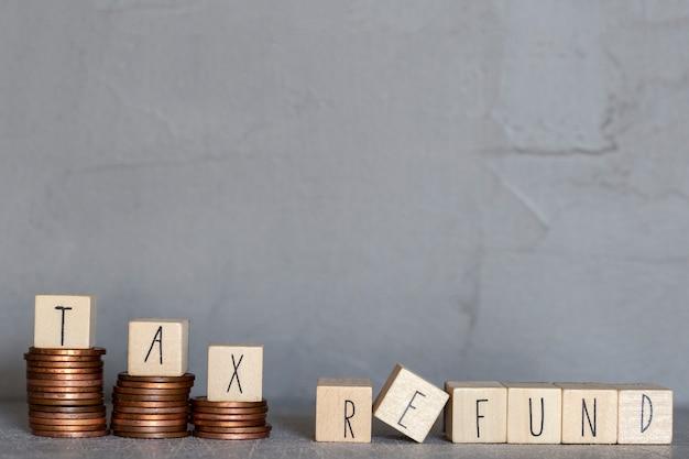 Texte de remboursement d'impôt avec des cubes en bois sur un mur de béton et des pièces d'empilage