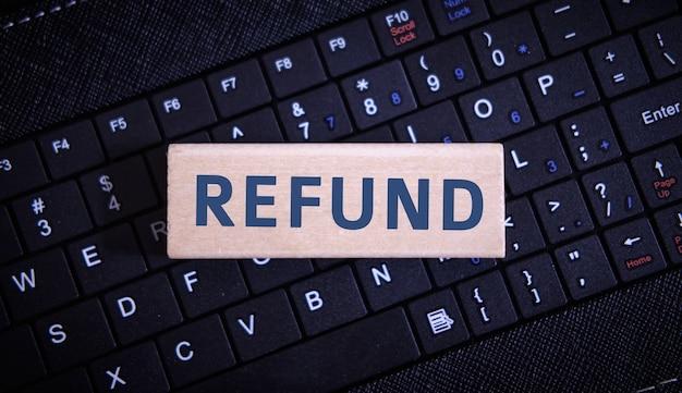 Texte de remboursement sur un objet en bois sur un clavier noir