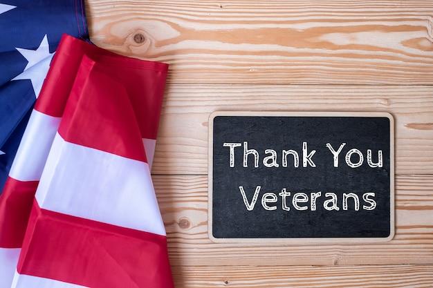 Texte de remerciement aux anciens combattants écrit au tableau avec le drapeau des états-unis