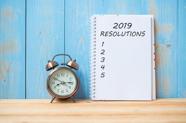 Texte des résolutions de 2019 sur un cahier et réveil rétro sur une table