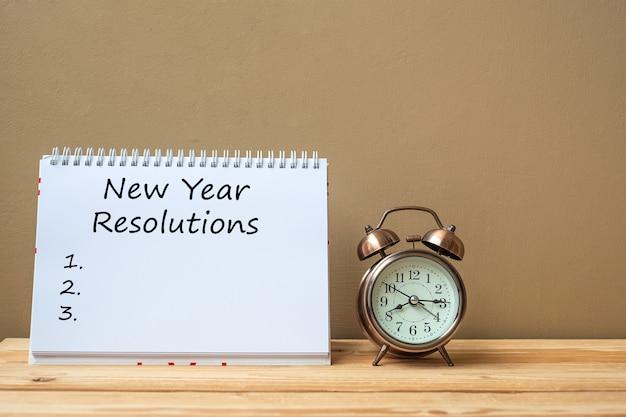 Texte de résolutions du nouvel an sur le cahier et le réveil rétro sur la table