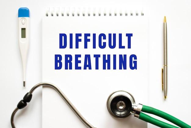 Texte de respiration difficile écrit dans un ordinateur portable posé sur un bureau et un stéthoscope. concept médical.
