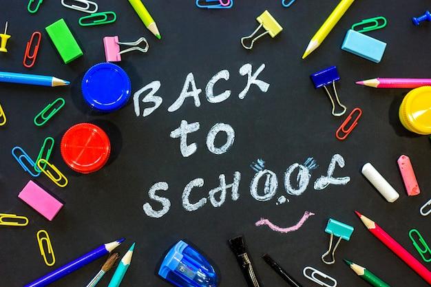 Texte de retour à l'école sur tableau noir et papeterie