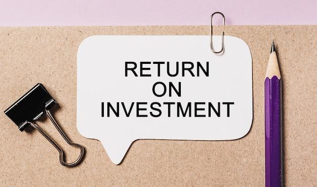 Texte de retour sur investissement sur un autocollant blanc avec de la papeterie de bureau