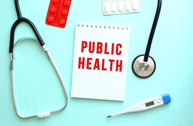 Le texte rouge santé publique est écrit sur un bloc-notes blanc qui se trouve à côté du stéthoscope sur un fond bleu.