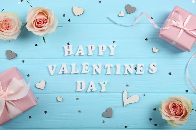 Texte de la saint valentin heureuse avec des cadeaux et des décorations sur fond bleu