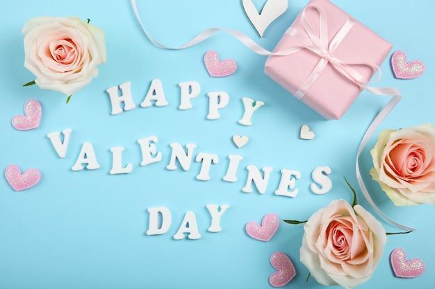Texte de la saint-valentin heureuse avec des roses roses et des coeurs sur fond bleu