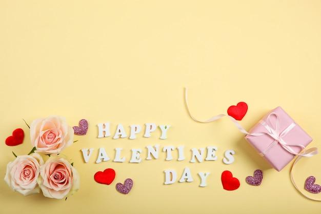 Texte de la saint-valentin heureuse avec des roses roses et des coeurs sur fond jaune