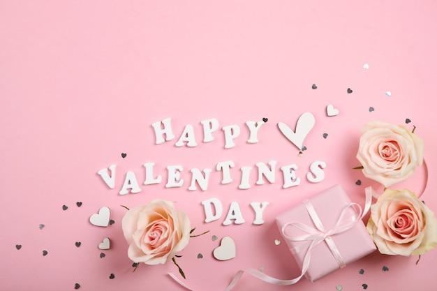 Texte de la saint-valentin heureuse avec des roses roses et des coeurs sur fond rose