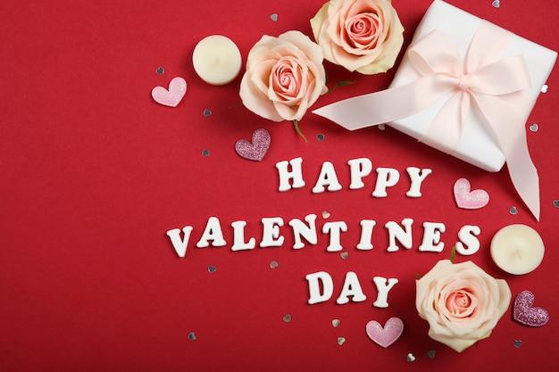 Texte de la saint-valentin heureuse avec des roses roses et des décorations sur fond rouge