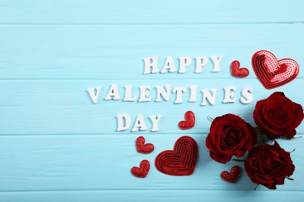 Texte de la saint-valentin heureuse avec des roses rouges et des coeurs sur fond bleu