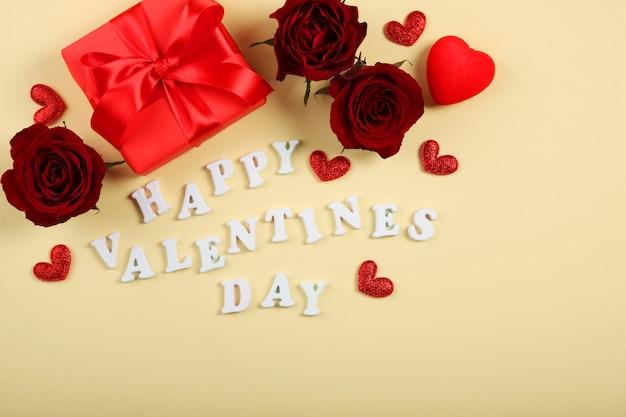 Texte de la saint-valentin heureuse avec des roses rouges et des coeurs sur fond jaune