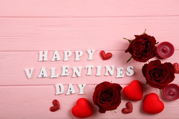 Texte de la saint-valentin heureuse avec des roses rouges et des coeurs sur fond rose