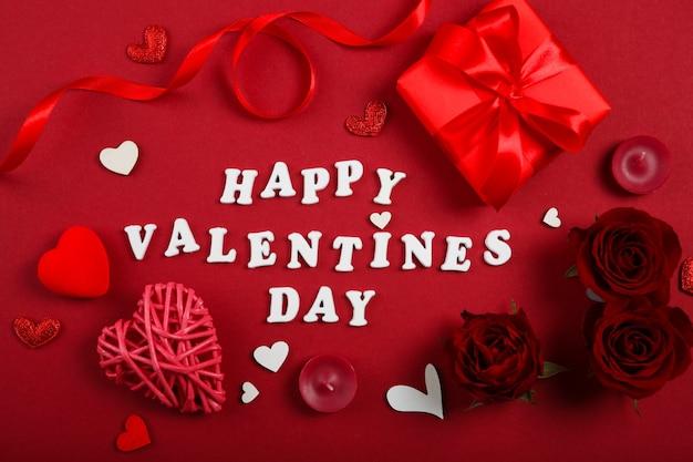 Texte de la saint-valentin heureuse avec des roses rouges et des décorations sur fond rouge
