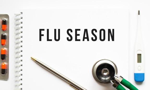Texte de la saison de la grippe écrit dans un ordinateur portable posé sur un bureau et un stéthoscope.