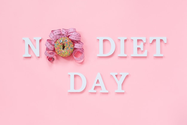 Texte sans jour de régime et visage drôle abstrait de femme de beignet avec les yeux et les cheveux de ruban de centimètre sur la plaque