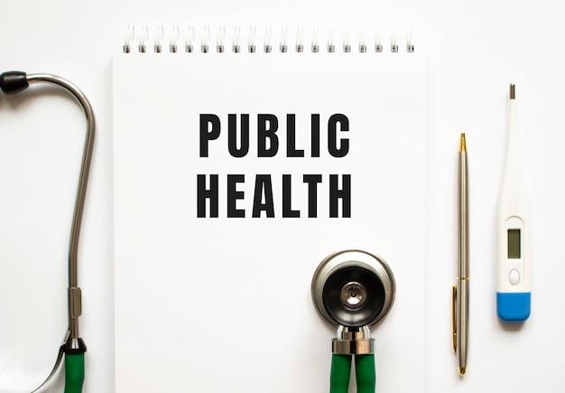Texte de santé publique écrit dans un ordinateur portable posé sur un bureau et un stéthoscope.