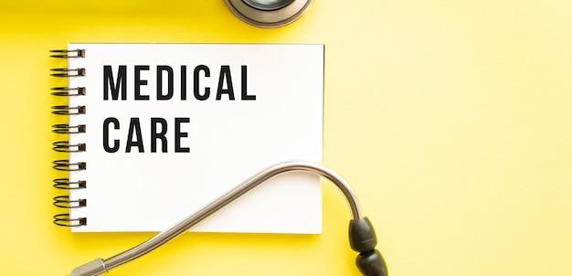 Texte soins médicaux sur ordinateur portable avec stéthoscope sur fond jaune. concept médical.