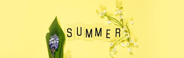 Texte summer à partir de lettres et de fleurs de camomille sur le mur jaune.