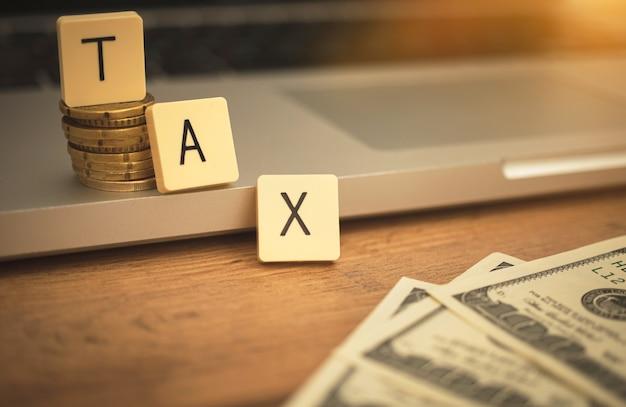 Texte de taxe sur le bureau avec ordinateur portable et billets d'un dollar. photo d'arrière-plan du concept de revenu bancaire