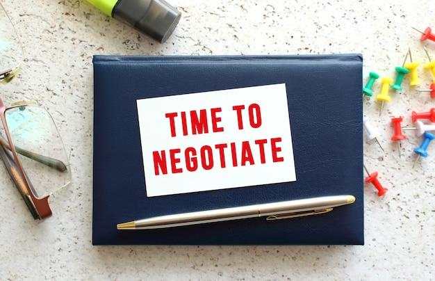 Texte temps de négociation sur une carte de visite posée sur un cahier bleu à côté des lunettes et de la papeterie.