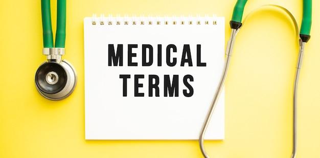 Texte termes médicaux sur ordinateur portable avec stéthoscope sur fond jaune. concept médical.