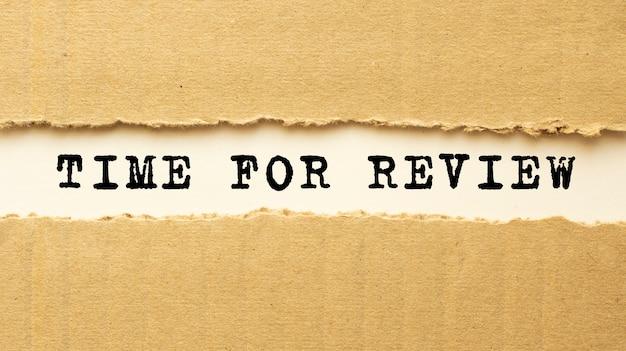 Texte time for review apparaissant derrière du papier brun déchiré. vue de dessus.