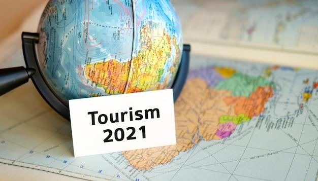Texte de tourisme sur une feuille blanche sur globe sur le fond bleu de la carte de l'atlas
