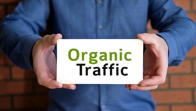 Texte de trafic de référencement organique entre les mains d'un jeune homme dans une chemise bleue