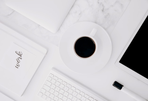 Texte de travail sur le journal; tablette numérique; tasse à café; clavier et marqueur noir sur le bureau blanc
