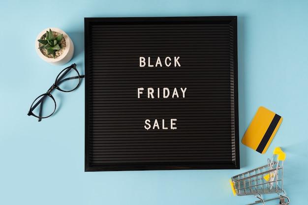 Texte vendredi noir sur tableau noir, cadeau, panier et carte de crédit. temps de vente de la saison de concept.