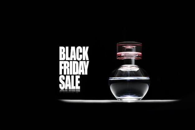 Texte de vente vendredi noir et bouteille de parfum ronde sur fond noir.