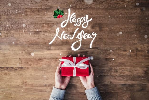 Texte de voeux de bonne année et cadeau sur fond de bois