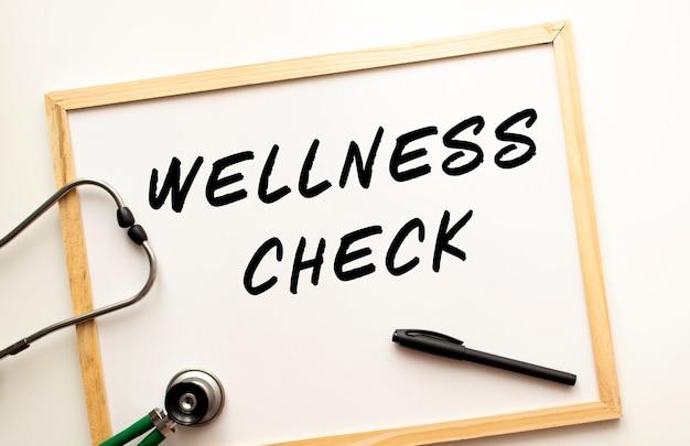 Le texte wellness check écrit sur un tableau blanc avec un marqueur