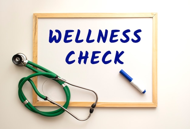 Le texte wellness check est écrit sur un tableau blanc avec un marqueur. a proximité se trouve un stéthoscope. concept médical.