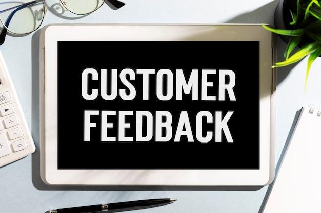 Textez les commentaires des clients sur une tablette, un stylo, des lunettes, une plante. concept d'entreprise. mise à plat.