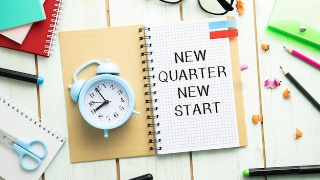 Textez new quarter new start sur la page blanche du bloc-notes. vue de dessus de bureau de table, mise à plat
