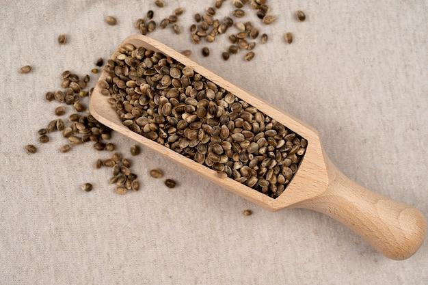 Textile texturé de chanvre sur un fond avec une pelle avec des graines de chanvre pelle avec des graines de chanvre texture de chanvre