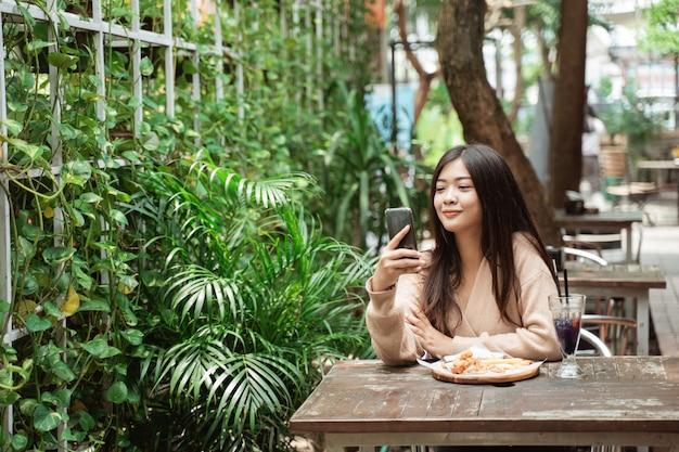 Texto femme sur téléphone mobile dans le café