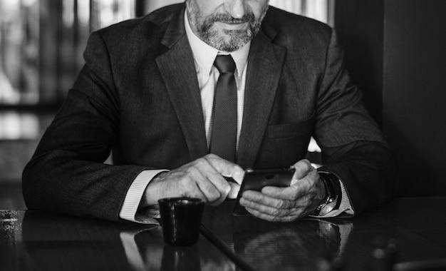 Textos homme d'affaires sur son téléphone portable