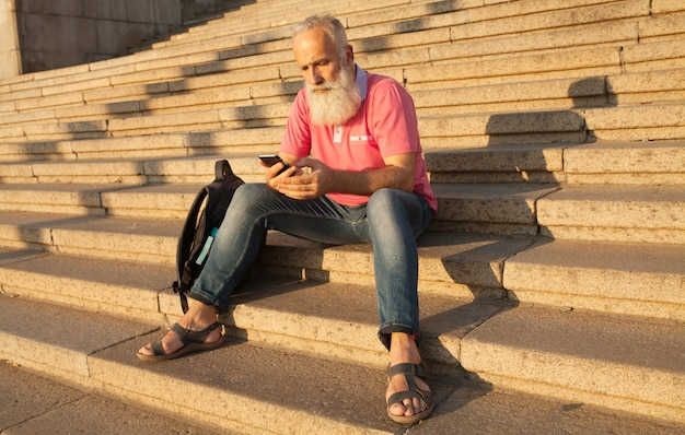 Textos de l'homme sur le téléphone. homme senior moderne avec mobile dans la rue, assis dans les escaliers.