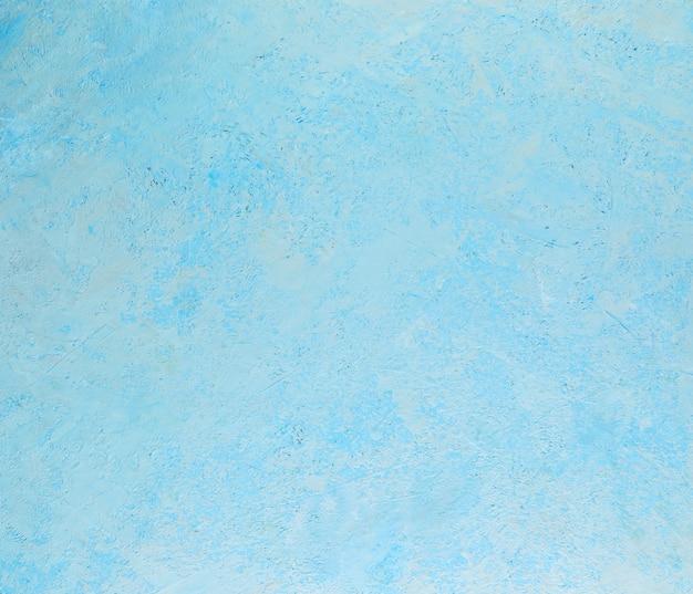 Texture abstraite de fond de plâtre rugueux avec des touches blanches de bleu.