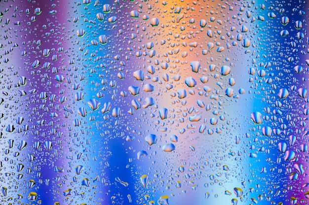 Texture abstraite gouttes d'eau sur le verre avec bleu et violet