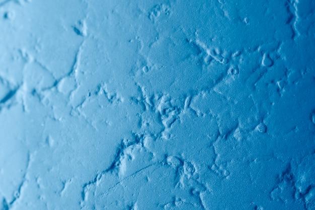 Texture abstraite d'un mur bleu avec des fissures. mastic décoratif pour béton avec place pour le texte.