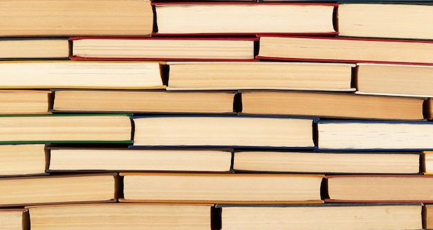 Texture abstraite de piles de divers livres cartonnés