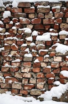 La texture de l'ancien mur de briques, recouvert d'une épaisse couche de neige après une forte chute de neige