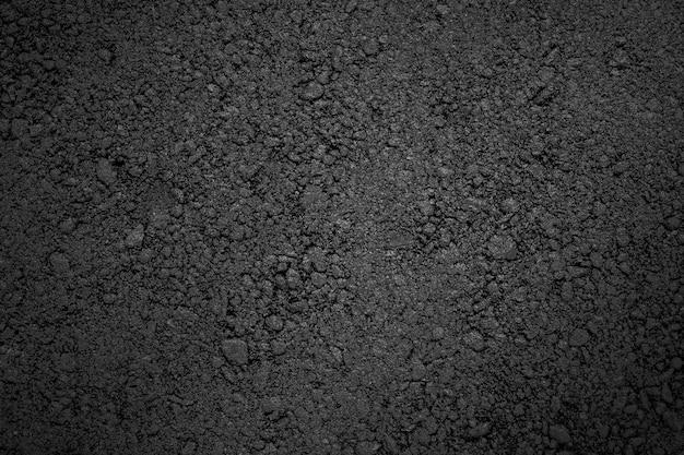 Texture d'asphalte, fond noir décoloré avec vignettage.