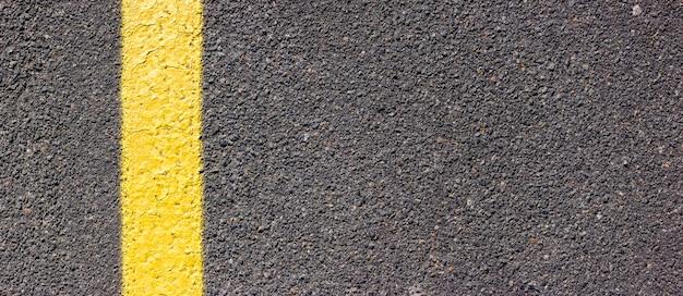 Texture asphalte avec une ligne jaune sur le côté gauche