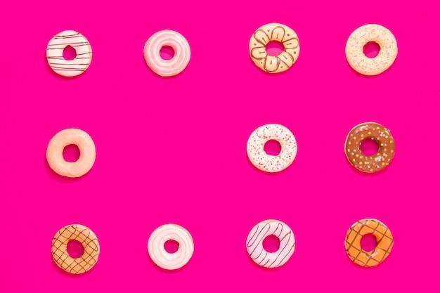 Texture de beignets multicolores sur fond rose. bonbons et nourriture